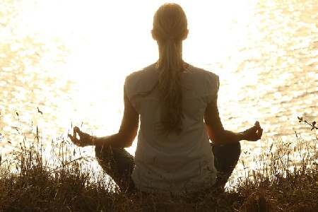 3 things to remember in order to stay young - woman meditating in front of a lake