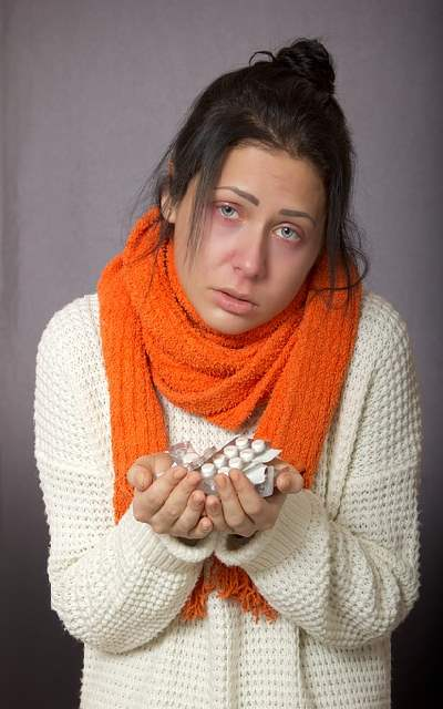 A sick woman holding a handful of medicines