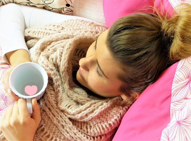 Sick woman holding a cup of tea lying in bed